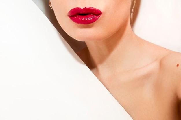 Menina moda glamourosa com lábios vermelhos em fundo branco.