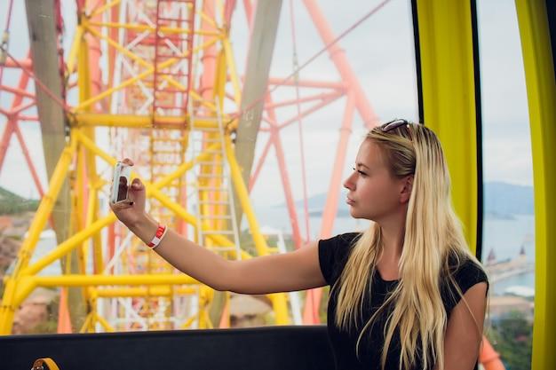 Menina moda jovem tirar selfie na roda gigante.