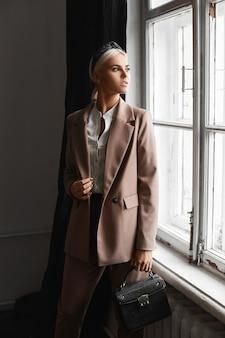 Menina modelo com cabelo loiro em um terno moderno, posando com uma bolsa da moda no interior vintage perto da janela