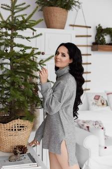 Menina modelo com longos cabelos negros em uma camisola longa posando em decoração para interior de natal