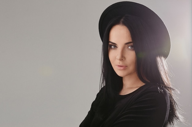 Menina modelo com maquiagem perfeita e cabelo preto, usando um chapéu preto isolado no fundo cinza com espaço de cópia