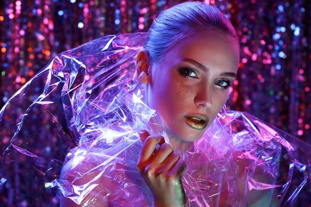 Menina modelo de alta moda em luzes de néon coloridas e brilhantes posando no estúdio através de filme transparente