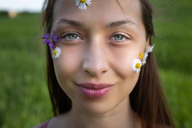 Menina modelo de beleza com flores silvestres e margaridas coladas em sua skin art fashion make up