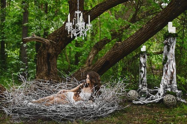 Menina modelo de cabelos castanho em lingerie repousa em um enorme ninho na floresta verde