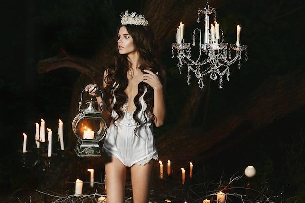 Menina modelo de lingerie com lanterna de vela na mão olha de lado e posando na floresta de mistério