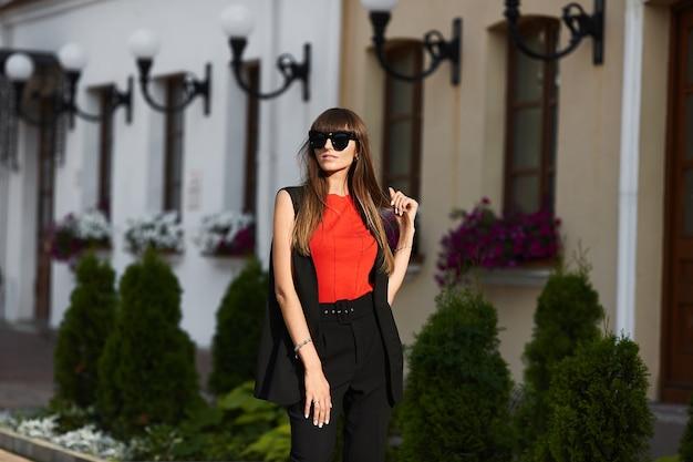 Menina modelo elegante com óculos de sol da moda e blusa vermelha andando pela rua da cidade em um dia ensolarado de verão
