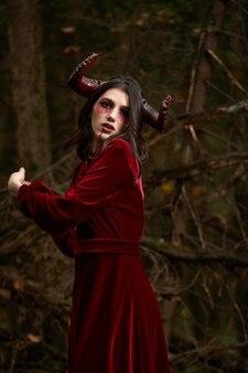 Menina modelo elegante e moderna na imagem de malévola posando entre a floresta mística - história de conto de fadas, cosplay. dia das bruxas.
