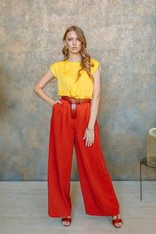 Menina modelo em calças vermelhas.