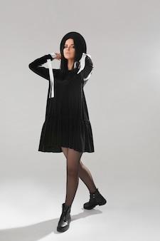 Menina modelo em um vestido preto curto e chapéu preto posando sobre fundo branco em estúdio de cosplay de bruxa para o halloween