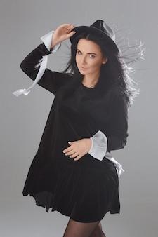 Menina modelo em um vestido preto curto e chapéu preto posando sobre fundo branco em estúdio de cosplay de wi ...
