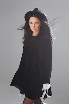 Menina modelo em um vestido preto curto e chapéu preto posando sobre fundo branco no estúdio. cosplay de bruxa para o halloween.