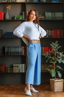 Menina modelo em uma blusa branca e calça azul, contra o fundo de estantes