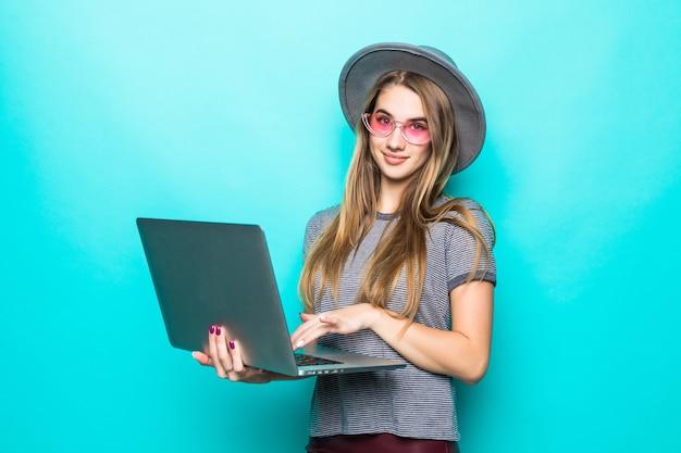 Menina modelo estudante sorridente em roupas da moda casuais funciona relógios em seu computador laptop isolado no verde