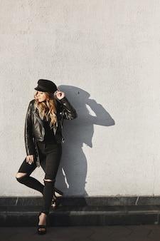 Menina modelo loira moderna em uma jaqueta de couro, jeans rasgados e boné preto em pé ao ar livre contra a parede urbana da cidade.