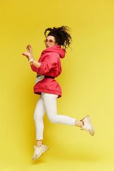 Menina modelo positiva em roupas esportivas casuais e óculos de sol pulando Foto Premium