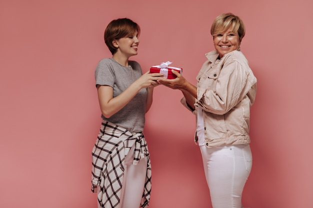 Menina moderna com penteado curto com roupas legais, dando uma caixa de presente vermelha para a senhora loira de jaqueta bege e calças leves no fundo rosa.