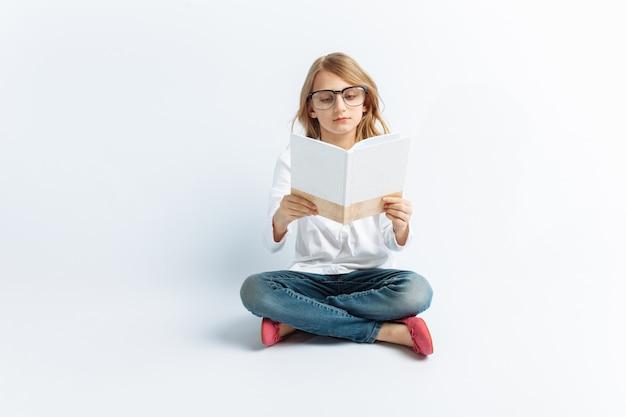 Menina moderna de óculos, lendo um livro e sonhando, bonito e bonito