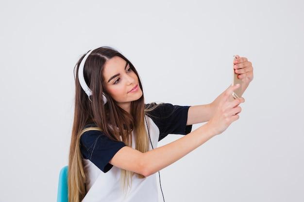 Menina moderna que leva selfie