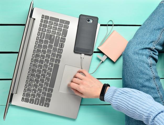 Menina moderna senta-se sobre um piso de madeira azul e usa um laptop. geração z. o conceito de freelancer. espaço de trabalho. vista do topo.