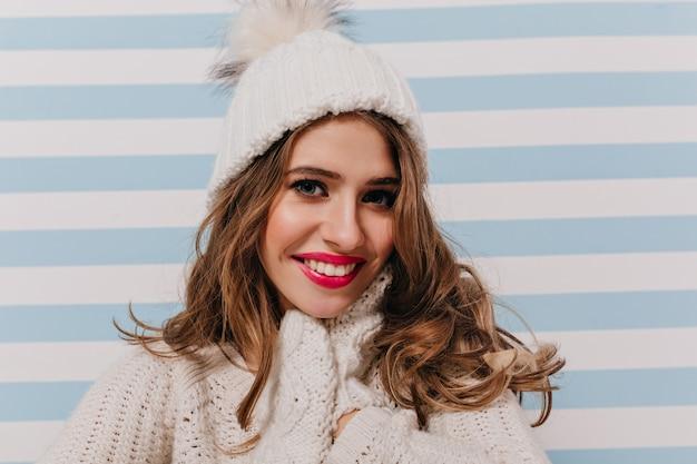 Menina modesta e gentil com linda maquiagem, sorriso doce, vestida com roupas de inverno e de bom humor, poses para retrato em close-up