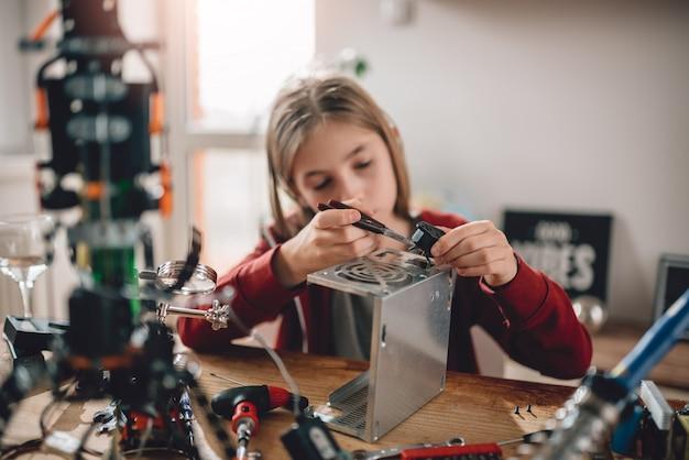 Menina modificando a fonte de alimentação e aprendendo robótica