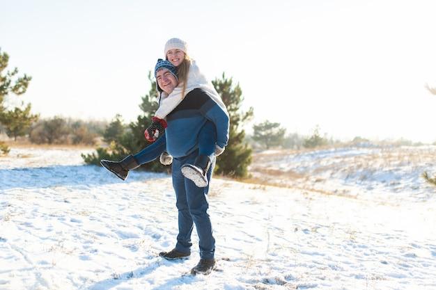 Menina monta um cara no fundo da árvore do abeto