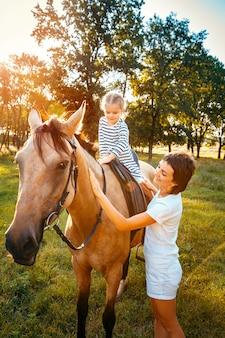 Menina, montando a cavalo com a mãe em pé nearb