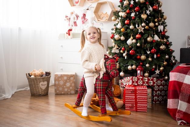 Menina, montando o cavalo de brinquedo em casa perto de caixas de árvore e presente de natal