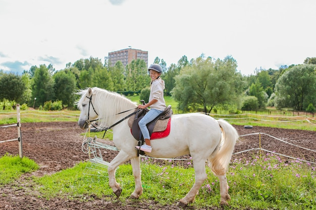 Menina montando um cavalo branco na natureza