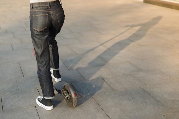 Menina, montando uma scooter elétrica ecofriendly em um parque em tempo ensolarado nas calçadas