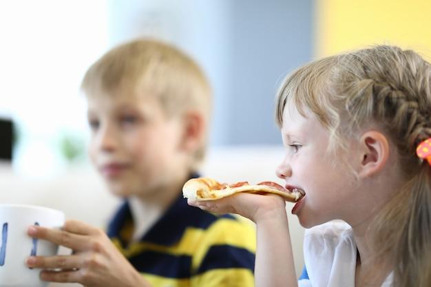 Menina morde o pedaço de pizza boy segurando uma xícara.