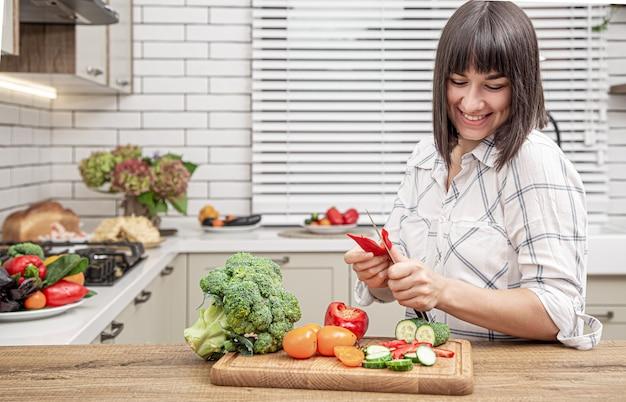 Menina morena alegre corta legumes na salada na parede do interior da cozinha moderna.