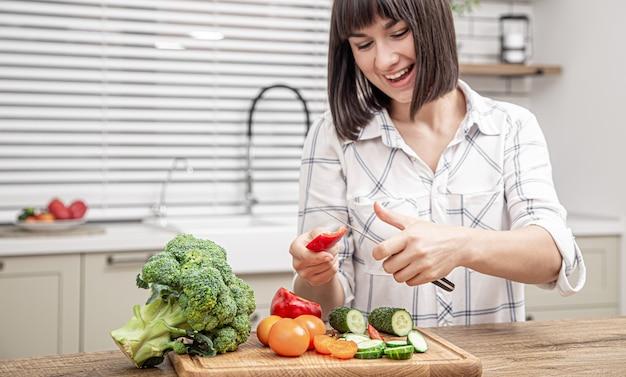 Menina morena alegre corta legumes na salada no fundo do interior da cozinha moderna.