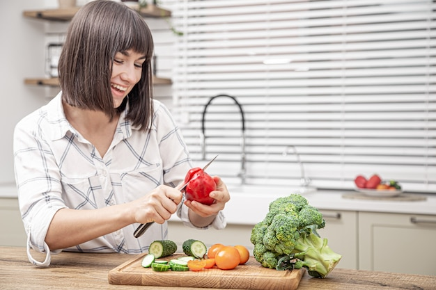 Menina morena alegre corta legumes na salada no interior da cozinha moderna.