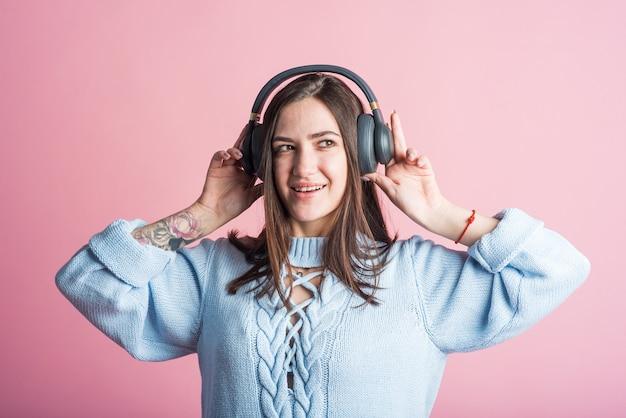 Menina morena alegre ouve música em fones de ouvido no estúdio em um fundo rosa