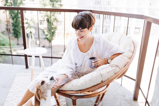 Menina morena alegre segurando uma xícara de café acariciando um cachorrinho engraçado que olha para cima com prazer
