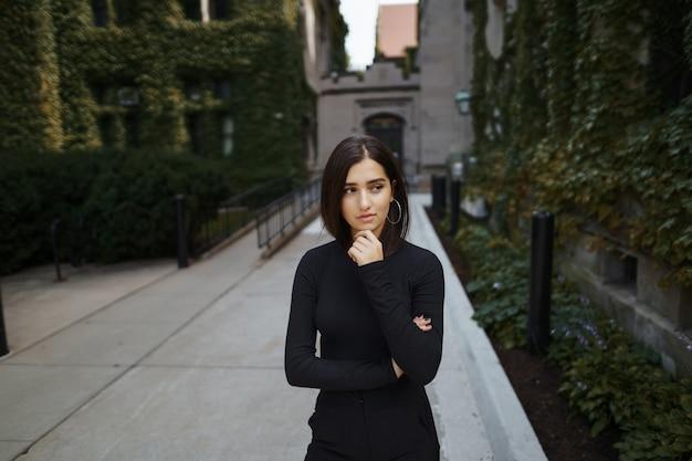 Menina morena andando pelo parque durante o outono