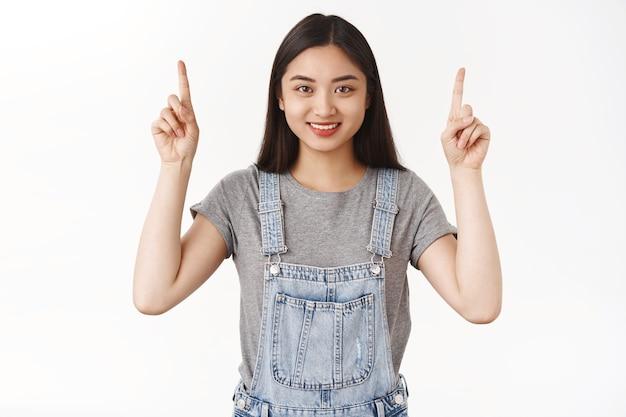 Menina morena asiática motivada, bonita, confiante, feliz, sorridente, apontando apenas para a frente, sucesso apontando para o dedo indicador sorriso câmera encantada propor promoção de oferta legal