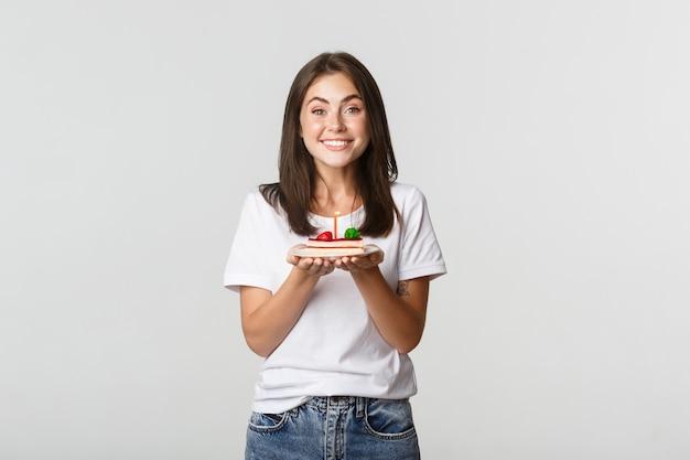 Menina morena atraente animada b-day fazendo desejo no bolo de aniversário, branco.