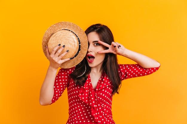 Menina morena atraente cobre parte do rosto com um chapéu. retrato de senhora de vestido de bolinhas, mostrando o símbolo da paz na parede amarela.