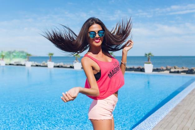 Menina morena atraente com cabelo comprido está pulando para a câmera perto da piscina. ela mostra emoções de garota feliz.