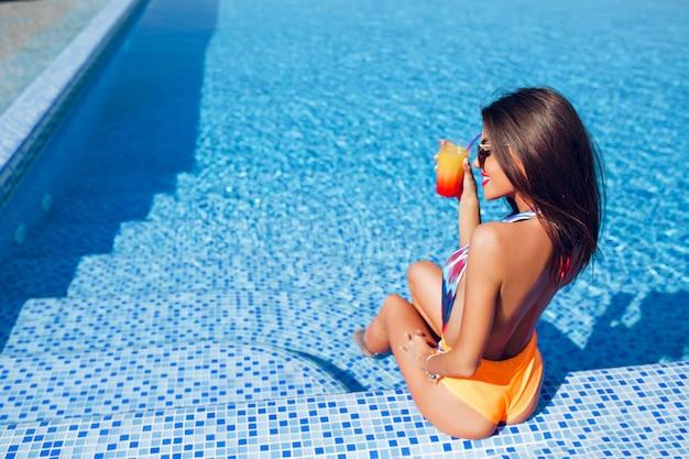 Menina morena atraente com cabelo comprido está sentada na escada para a piscina. ela está segurando um coquetel e sorrindo. visão horizontal de trás.