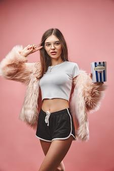 Menina morena atraente com pele rosa falsa, segurando pipoca na mão, vestindo shorts pretos e top branco.