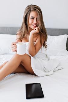 Menina morena atraente do retrato com pernas travessas na cama branca em apartamento moderno. ela segura a xícara, sorrindo.