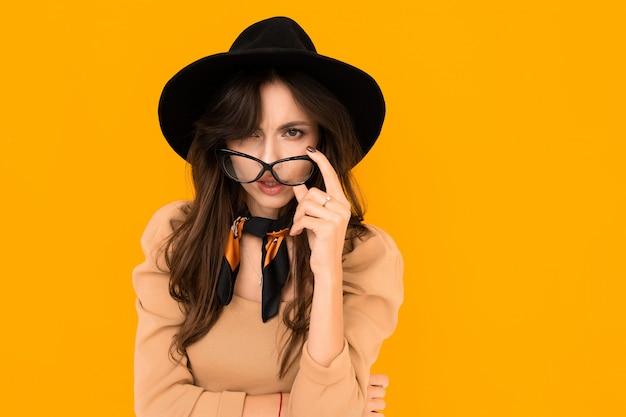 Menina morena atraente em um chapéu preto e blusa e com óculos em uma parede amarela