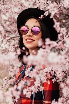 Menina morena atraente perto de uma árvore de amêndoa