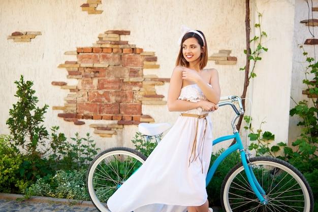 Menina morena atraente posando perto de bicicleta azul, olhando para o lado em frente ao antigo prédio de tijolos