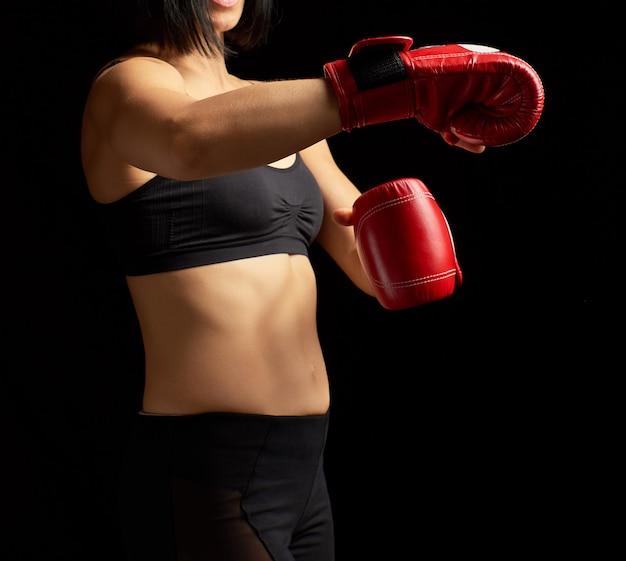 Menina morena bonita de aparência desportiva em um sutiã preto e caneleiras
