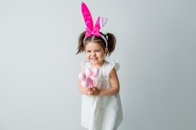 Menina morena bonitinha sorrindo com as orelhas de um coelho na cabeça segurando ovos de páscoa decorativos contra um fundo claro. conceito de páscoa, espaço para texto
