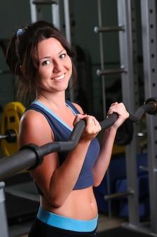 Menina morena branca e sorridente em pé, segurando uma barra com peso nas mãos